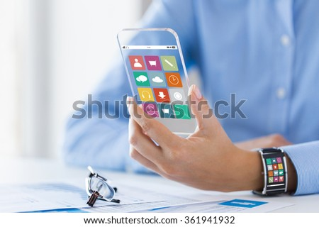 hand with app icons on smart phone and watch - stock photo