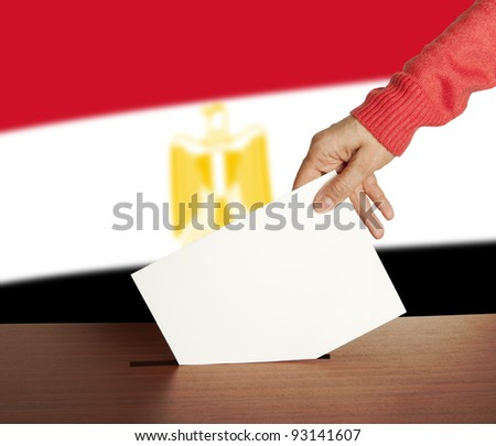 Hand with ballot and box on Flag of Egypt - stock photo
