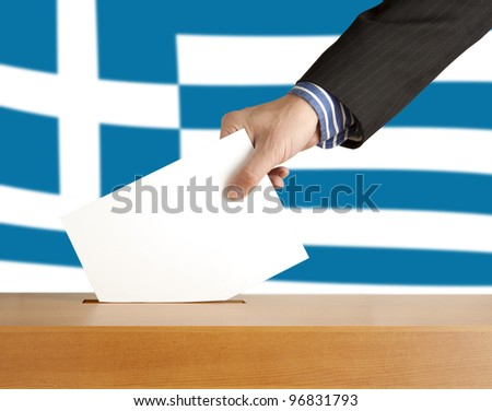 Hand with ballot and box on Flag of Greece - stock photo