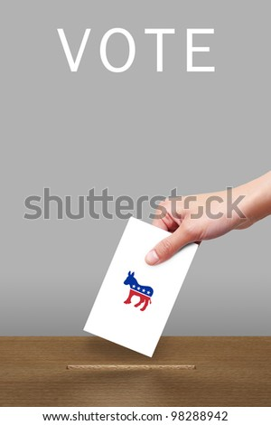 Hand with ballot and wooden box with Democratic party icon - stock photo
