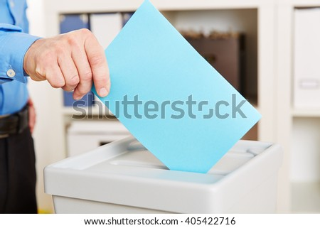 Hand with ballot paper an voting booth during election - stock photo