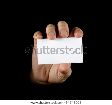 Hand with black business card on black background - stock photo