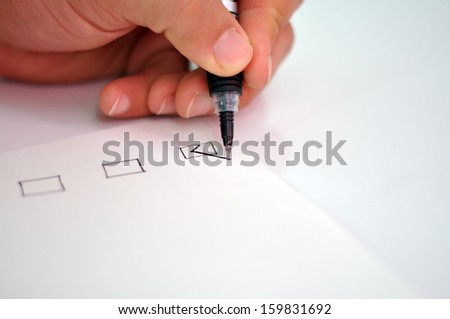 Hand with black pen marking a check box - stock photo