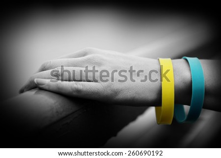 Hand with blue-yellow bracelet - colors of flag of Ukraine - stock photo