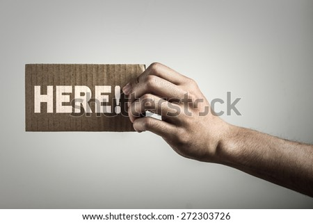 Hand with brown card is showing here with gray background. - stock photo