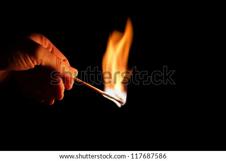 hand with burning match on black - stock photo