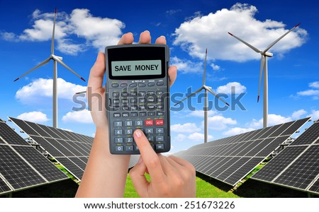 Hand with calculator. In the background solar energy panels and wind turbines.Concept of saving money. - stock photo