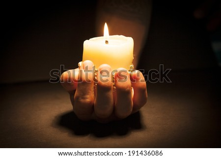 Hand with candle in black background - stock photo