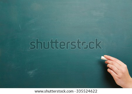Hand with chalk and empty green chalkboard as background