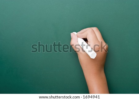 Hand with chalk writing on a green chalkboard horizontal format