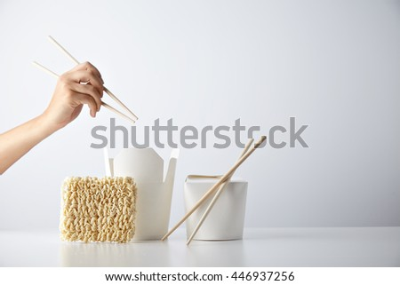 Hand with chopsticks ready above opened and closed takeaway boxes, brick of japanese egg noodles presented with chopsticks, isolated on white Retail set - stock photo