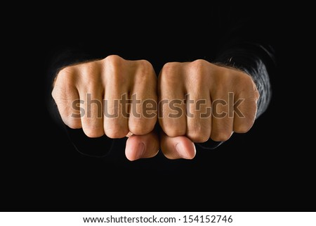 Hand with clenched fist on dark background. Power, determination, resistance concept.