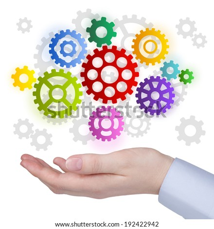 Hand with colorful cog weels on white - stock photo