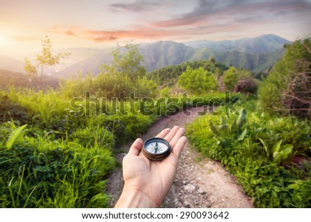 Hand with compass at mountain road at sunset sky in Kazakhstan, central Asia