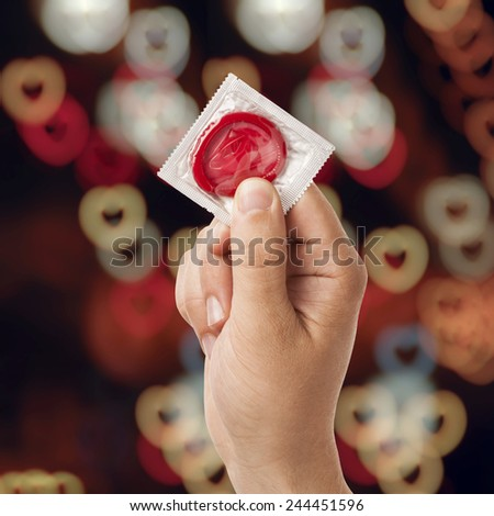 Hand with condom isolated on hearts bokeh background, Valentine's day - stock photo