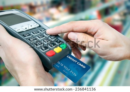 Hand with credit card swipe through terminal for sale in supermarket - stock photo