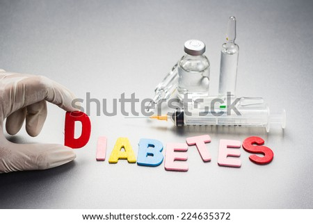 Hand with diabetes word and medical equipment - stock photo