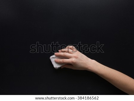 Hand with dry sponge on matte gray surface