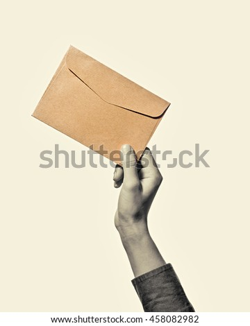 Hand with envelope from kraft paper, isolated, toned, black and white - stock photo
