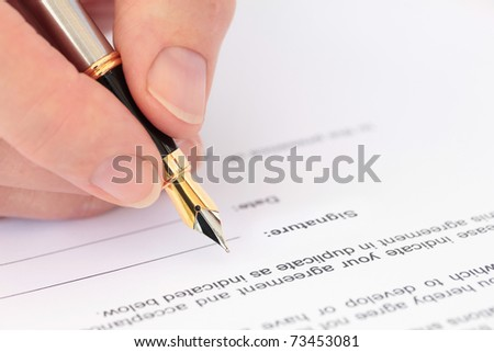 Hand with Fountain Pen Signing a Document - stock photo