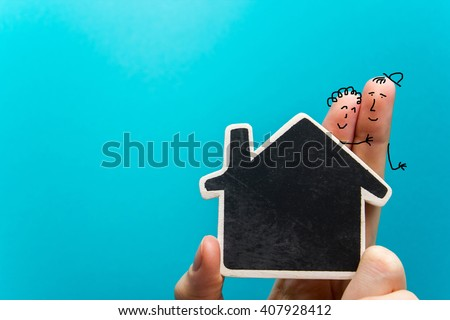 Hand with funny fingers holding white paper house figure on blue background. Real Estate Concept. Copy space top view. - stock photo