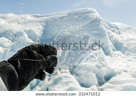 Hand with glove holding a transparent ice piece with snow and ice background - stock photo