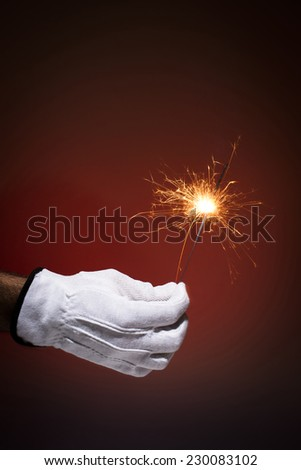 Hand with glove, holding sparkler on red background.