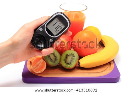 Hand with glucose meter, fresh ripe natural fruits and glass of juice on cutting board, concept for diabetes, healthy nutrition and strengthening immunity