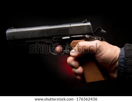 Hand with gun on a dark  background - stock photo