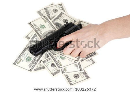 hand with gun on hundred-dollar bills