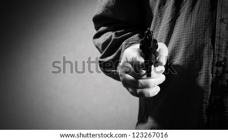Hand with gun ready to shoot - stock photo