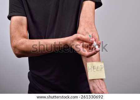Hand with heroin syringe with post it that says help - stock photo