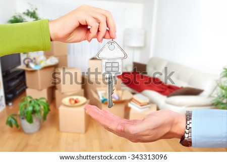 Hand with house key. Real estate and moving background. - stock photo