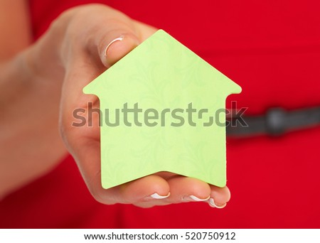 Hand with house sticky note.