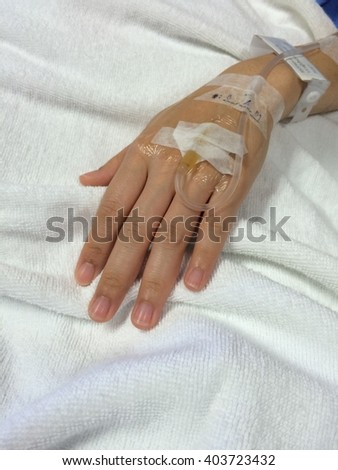 Hand with IV drip needle, patient lying on bed in hospital for medical care background