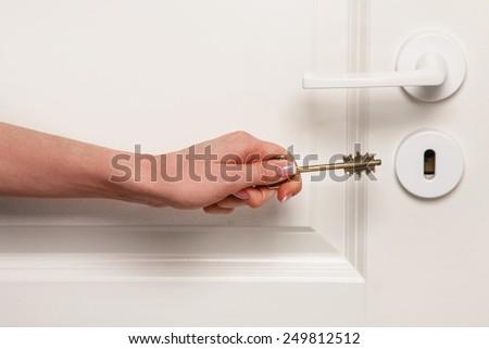 Hand with key beside the door - stock photo