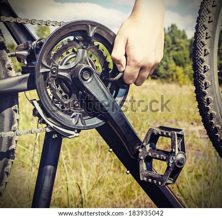 hand with key repairs bicycle against the sky. toned image - stock photo
