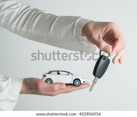 Hand with keys and car on white background. Car insurance. Automobile collision damage waiver concepts. with protective gesture and icon of car. Protection of car. Business concept. - stock photo