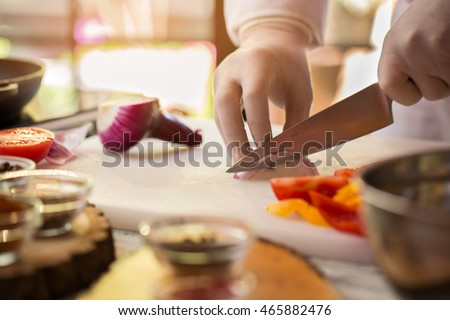 Hand with knife cutting onion. Colorful vegetables on cooking board. Key ingredient of spicy soup. Working time in the kitchen.