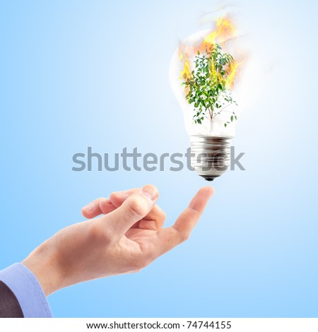 Hand with lamp and plant in fire. Concept - save nature. Collage