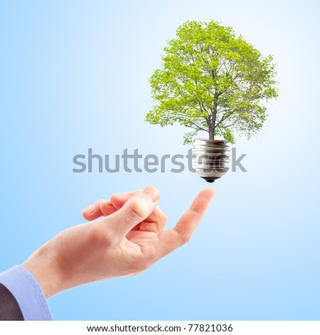 Hand with lamp and tree. Concept of renewable energy - stock photo
