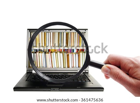 Hand with magnifying glass looking at laptop with books  - stock photo