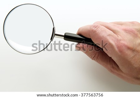 Hand with Magnifying glass on white plane - stock photo