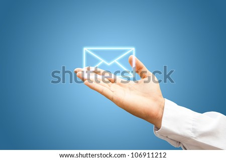 Hand with mail symbol on blue background - stock photo