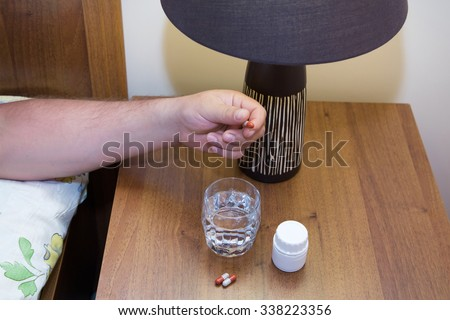 Hand with medicine and a glass of water on the nightstand