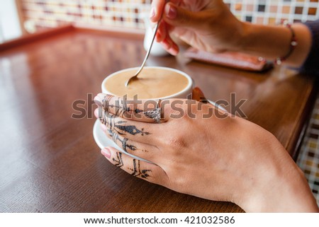 hand with mehendi picture holding a coffee in the cafe
