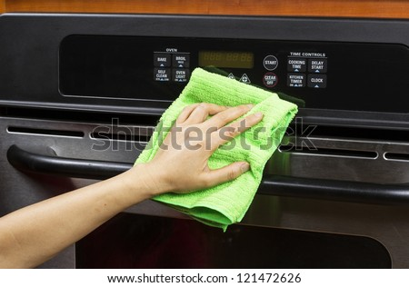 Hand with microfiber cleaning rag wiping outside of electric oven - stock photo