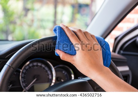 Hand with microfiber cloth cleaning Interior and steering wheel modern car. - stock photo