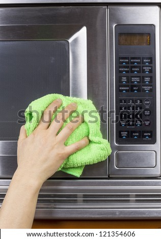 Hand with microfiber rag cleaning outside of microwave oven - stock photo
