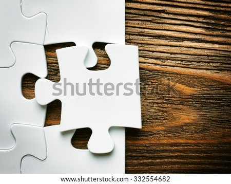 Hand with missing jigsaw puzzle piece. Business concept image for completing the final puzzle piece.wooden background - stock photo